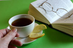 Refreshing Read. Hand reaching for cup of tea with lemon and book with glasses Royalty Free Stock Photo