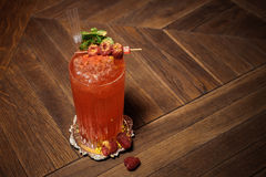 Refreshing red cocktail beverage with a sprig of fresh mint leaves and raspberries. Refreshing red cocktail beverage with a sprig of fresh mint leaves and Stock Image