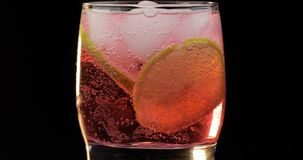 Refreshing red drink cocktail in a glass with ice, and lime. Soda fizzy water stock photos