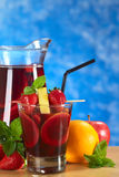 Refreshing Sangria. Refreshing red wine punch called sangria mixed with orange, apple and mango, garnished with strawberries and pineapple on skewer with a jug Stock Photography