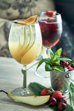Refreshing sangria or punch with fruits in glass and pincher jpg Stock Images