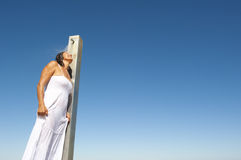 Refreshing shower for sexy woman at the ocean. Upward view of A sexy looking mature woman in her fifties, wearing a white summer dress and having a refreshing Royalty Free Stock Photography