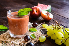 Refreshing smoothie with grape, watermelon and peach. Organic smoothie with grape, watermelon and peach in a glass jar Royalty Free Stock Photography