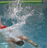 Refreshing splash. Man diving into a swimming pool creating a large splash of water Stock Photo