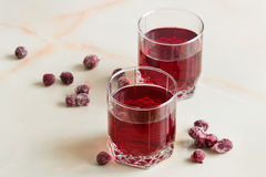 Refreshing summer cherry juice with berries on the table in a gl. A refreshing summer red berry juice in a glass on a light background Stock Images