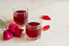 Refreshing summer cherry juice with berries on the table in the. A refreshing summer red berry juice in a glass on a light background Royalty Free Stock Images