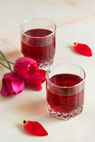 Refreshing summer cherry juice with berries on the table in the. A refreshing summer red berry juice in a glass on a light background Stock Image