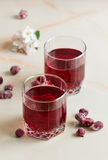Refreshing summer cherry juice with berries on the table. A refreshing summer red berry juice in a glass on a light background Stock Images