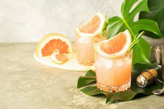 A refreshing summer cocktail of grapefruit champagne juice glass goblets gray concrete background with monster leaves. stock photography