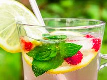 Refreshing summer cocktail with lemon, raspberry and mint close-up stock photography