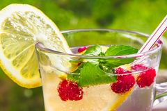 Refreshing summer cocktail with lemon, raspberry and mint close-up stock images