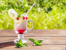 Refreshing summer cocktail with lemon, raspberry and mint a wooden table stock image