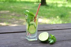 Refreshing summer cold drinks Sassy water with lemon, lime, cucumber, mint, ginger in glass on wooden table, outdoor. stock images