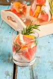 Refreshing summer detox cocktail of grapefruit and rosemary, on Royalty Free Stock Photos