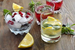 Refreshing summer drink with berries and lemon in a glass Stock Photos