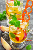 Refreshing summer drink Peach Sweet Tea with ice and mint Royalty Free Stock Photos