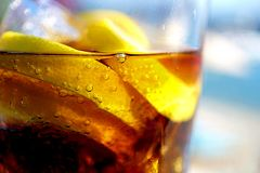 Summer Drink on the Rocks. Refreshing summer drink with sparkling bubbles, ice cubes and lemon siices stock image
