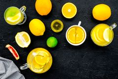 Refreshing summer tea with fruits. Teacup and teapot near orange, lime, lemon, grapefruit on black background top view.  Royalty Free Stock Images