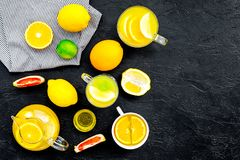 Refreshing summer tea with fruits. Teacup and teapot near orange, lime, lemon, grapefruit on black background top view.  Stock Photo
