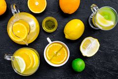 Refreshing summer tea with fruits. Teacup and teapot near orange, lime, lemon, grapefruit on black background top view.  Royalty Free Stock Photo