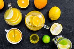 Refreshing summer tea with fruits. Teacup and teapot near orange, lime, lemon, grapefruit on black background top view.  Stock Photos