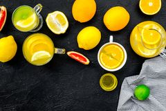 Refreshing summer tea with fruits. Teacup and teapot near orange, lime, lemon, grapefruit on black background top view.  Stock Image