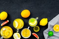 Refreshing summer tea with fruits. Teacup and teapot near orange, lime, lemon, grapefruit on black background top view.  Stock Photography
