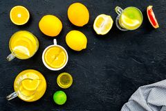 Refreshing summer tea with fruits. Teacup and teapot near orange, lime, lemon, grapefruit on black background top view.  Stock Images