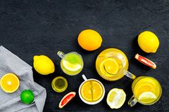 Refreshing summer tea with fruits. Teacup and teapot near orange, lime, lemon, grapefruit on black background top view.  Royalty Free Stock Photography