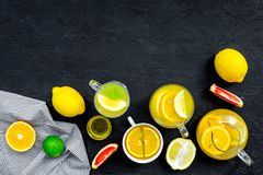 Refreshing summer tea with fruits. Teacup and teapot near orange, lime, lemon, grapefruit on black background top view.  Royalty Free Stock Photos