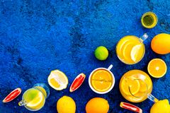Refreshing summer tea with fruits. Teacup and teapot near orange, lime, lemon, grapefruit on blue background top view.  Royalty Free Stock Images