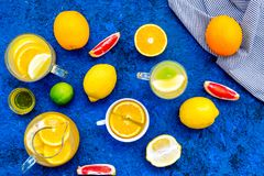 Refreshing summer tea with fruits. Teacup and teapot near orange, lime, lemon, grapefruit on blue background top view.  Royalty Free Stock Photography