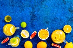 Refreshing summer tea with fruits. Teacup and teapot near orange, lime, lemon, grapefruit on blue background top view.  Stock Photo