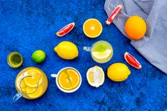 Refreshing summer tea with fruits. Teacup and teapot near orange, lime, lemon, grapefruit on blue background top view.  Stock Photos