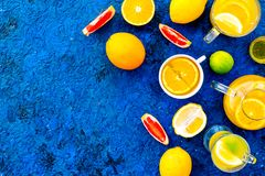 Refreshing summer tea with fruits. Teacup and teapot near orange, lime, lemon, grapefruit on blue background top view.  Royalty Free Stock Photo