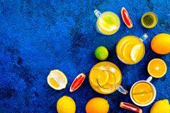 Refreshing summer tea with fruits. Teacup and teapot near orange, lime, lemon, grapefruit on blue background top view.  Stock Image