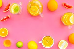 Refreshing summer tea with fruits. Teacup and teapot near orange, lime, lemon, grapefruit on pink background top view.  Stock Images