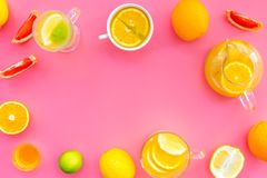 Refreshing summer tea with fruits. Teacup and teapot near orange, lime, lemon, grapefruit on pink background top view.  Royalty Free Stock Photography