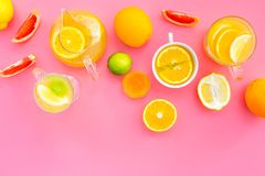 Refreshing summer tea with fruits. Teacup and teapot near orange, lime, lemon, grapefruit on pink background top view.  Stock Photo