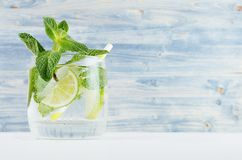 Refreshing transparent spring drink with slices lime, twig mint, ice, bubbled water, straw on soft blue wood plank, copy space. Stock Image