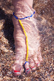 Refreshing water. Decorated foot of a young woman in the sea water Royalty Free Stock Photos