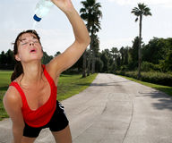 Refreshing water. Active woman cooling down by pouring water on her face Royalty Free Stock Photography