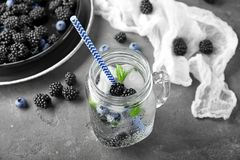 Refreshing water with blackberries in mason jar. On table Royalty Free Stock Photo