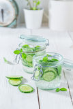 Refreshing water in jar with cucumber and mint leaves Stock Images