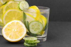 Water with lemon and cucumber and mint in a glass cup and in a jug next to half a fresh lemon and cucumber slices on a black backg royalty free stock images