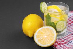Water with lemon and cucumber and mint in a glass cup next to half a fresh lemon and cucumber slices on a black background royalty free stock photography
