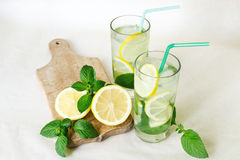 Refreshing water with lemon, mint leaves and ice in glass glasses with colored tubules. Lemon with mint branches on a wooden board Stock Image