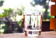 Refreshing water in transparent glass  against with greeneries b Royalty Free Stock Images