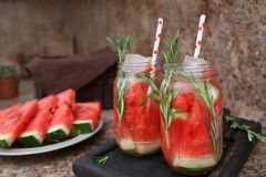 Refreshing watermelon cocktail with rosemary served with ice. Two jars of refreshing summer drink with watermelon and rosemary against a dark background stock images