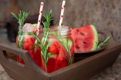 Refreshing watermelon cocktail with rosemary served with ice. Two jars of refreshing summer drink with watermelon and rosemary served on a wooden tray stock image